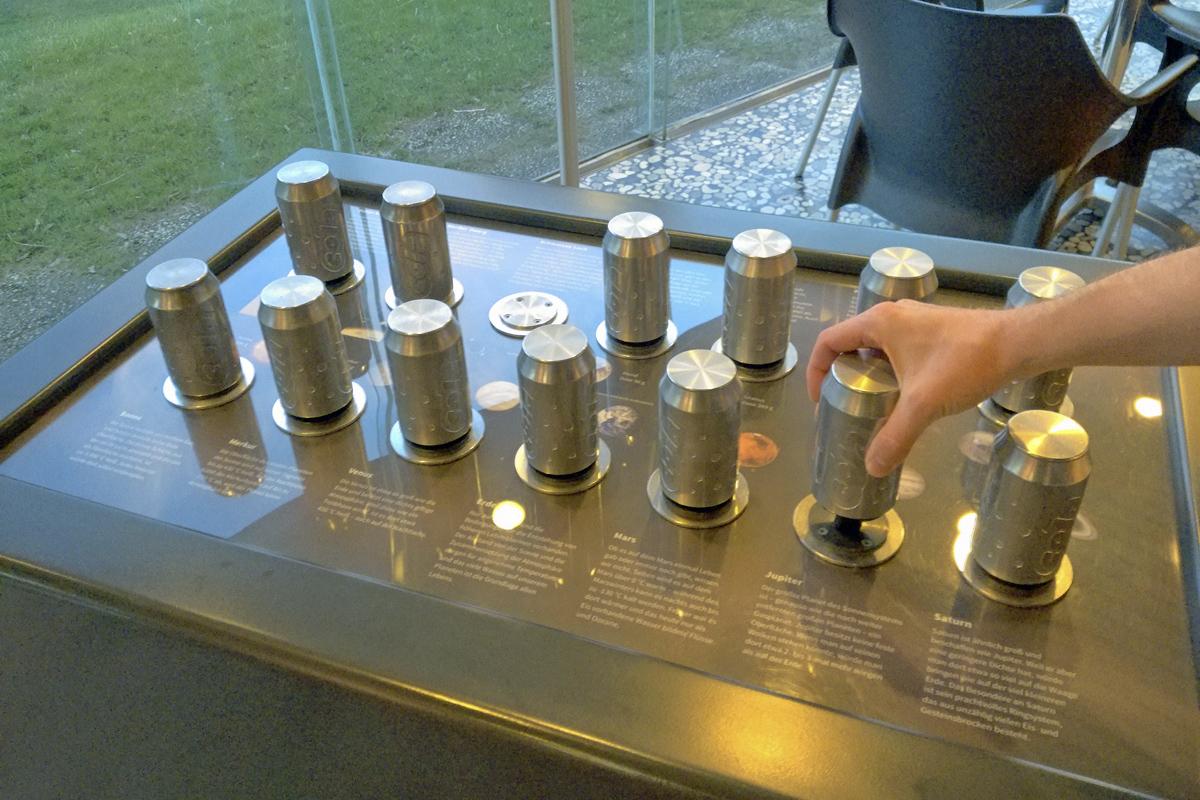 Das Foto zeigt ein Experiment im Eingangsbereich des Zeiss Planetariums in Bochum, mit dem anhand von Dosen die Schwerkraft auf verschiedenen Planeten für Besucher erlebbar gemacht wird.