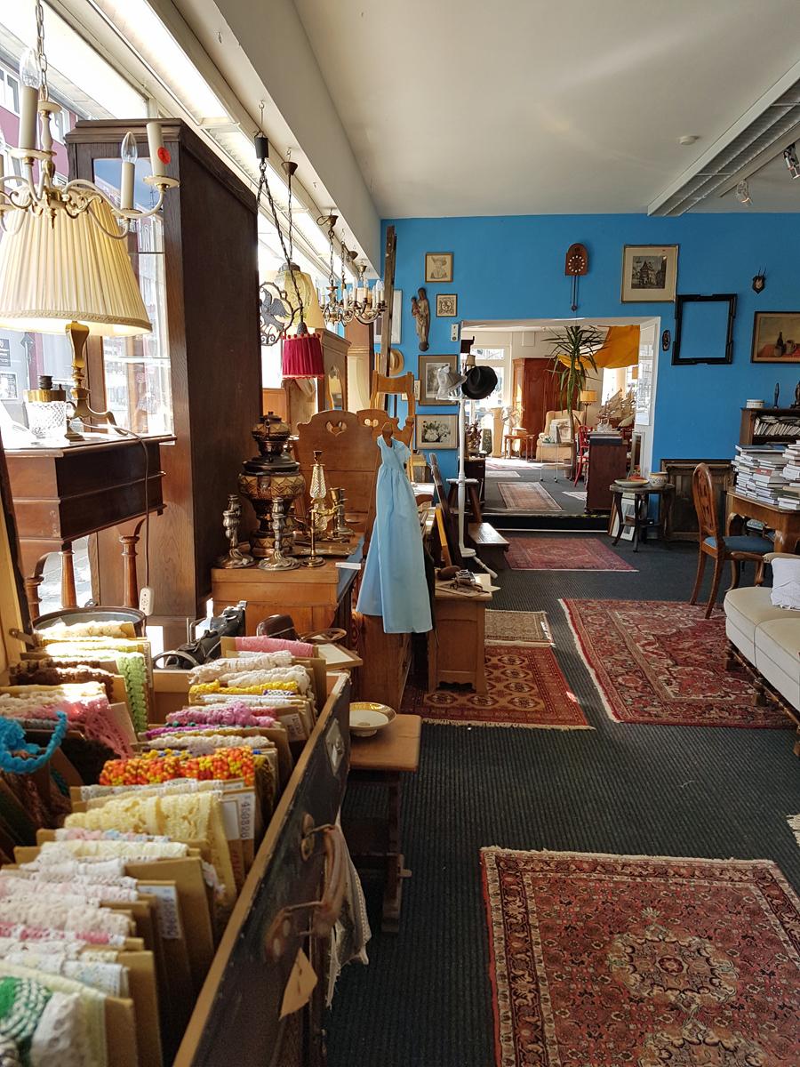 Das Foto zeigt einen Teil der Verkaufsfläsche mit einer bunten Mischung aus Möbeln, Bildern und Dekoartikeln im Vintage Geschäft Platz.Hirsch in Essen-Holsterhausen.