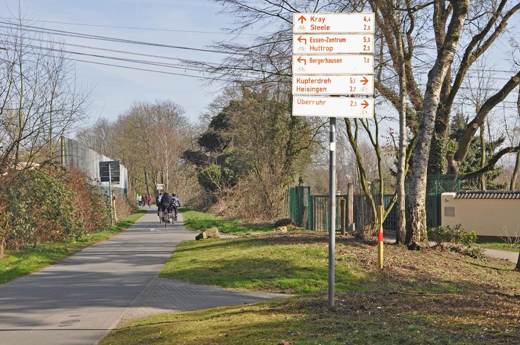 Das Foto zeigt einige Hinweisschilder für Radfahrer auf der Grugatrasse in Essen, auf der es sich fernab des Straßenverkehrs entspannt radeln lässt.