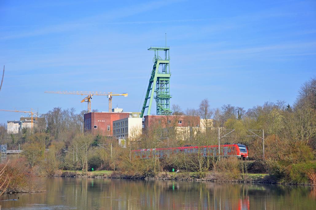 Das Foto zeigt auf der anderen Uferseite der Ruhr die Zeche Heinrich, die Radfahrer auf ihrer Tour durchs radrevier.ruhr auf dem RuhrtalRadweg erblicken.