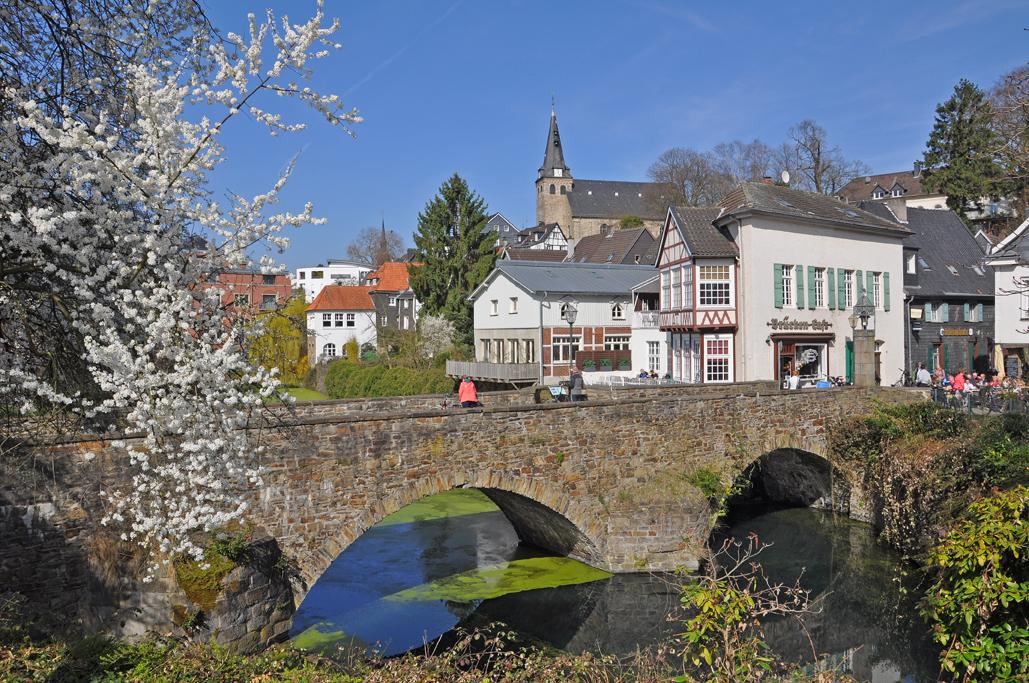 Das Foto zeigt die hübsche Altstadt von Essen-Kettwig hinter einer schön geschlungenen Brücke über der Ruhr.