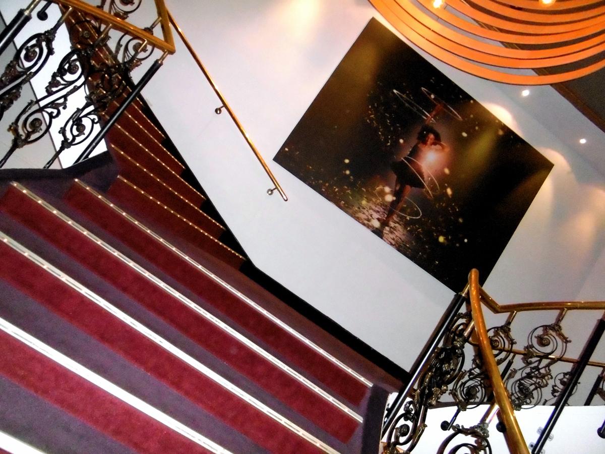 Das Foto zeigt die verschnörkelte Treppe mit vergoldetem Geländer im GOP Varieté-Theater Essen.