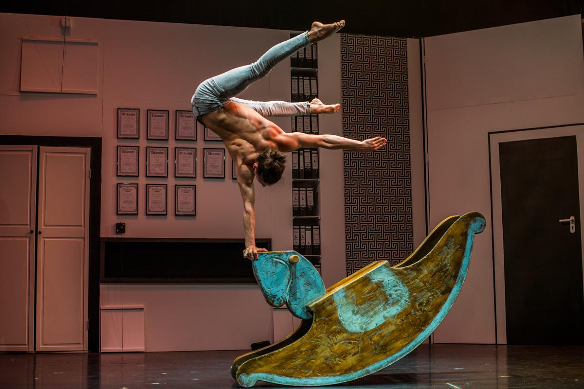 """Das Foto zeigt einen Artisten der Show """"KAWUMM"""" im GOP Varieté-Theater Essen, der mit seiner Muskelkraft auf einem Schaukelpferd balanciert."""