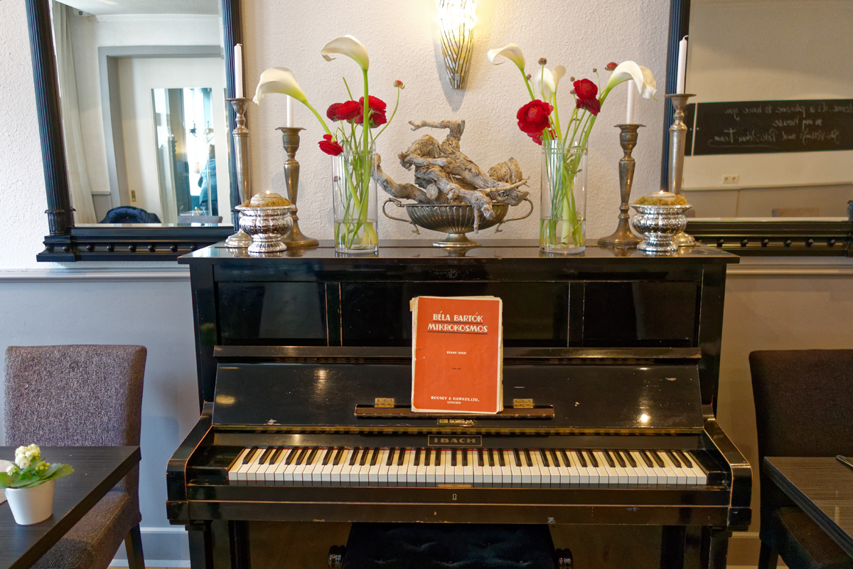 """Das Foto zeigt ein Klavier im gemütlichen Innenraum des Restaurants """"Petersilchen"""" in Xanten."""
