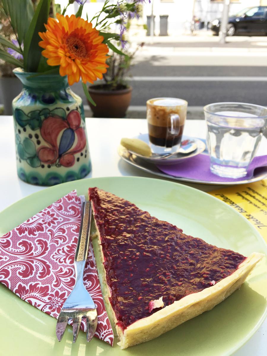 Das Foto zeigt ein Stück Himbeer Tarte und einen Espresso Macchiato vor einem Sträußchen Blumen im Café Fräulein Coffea in Bochum-Ehrenfeld.