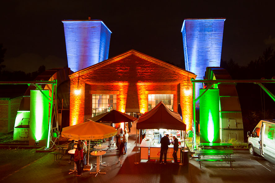 Das Foto zeigt das ExtraSchicht-Feeling an der Zeche Hannover in Bochum mit vielen bunten Illuminationen und Essenständen