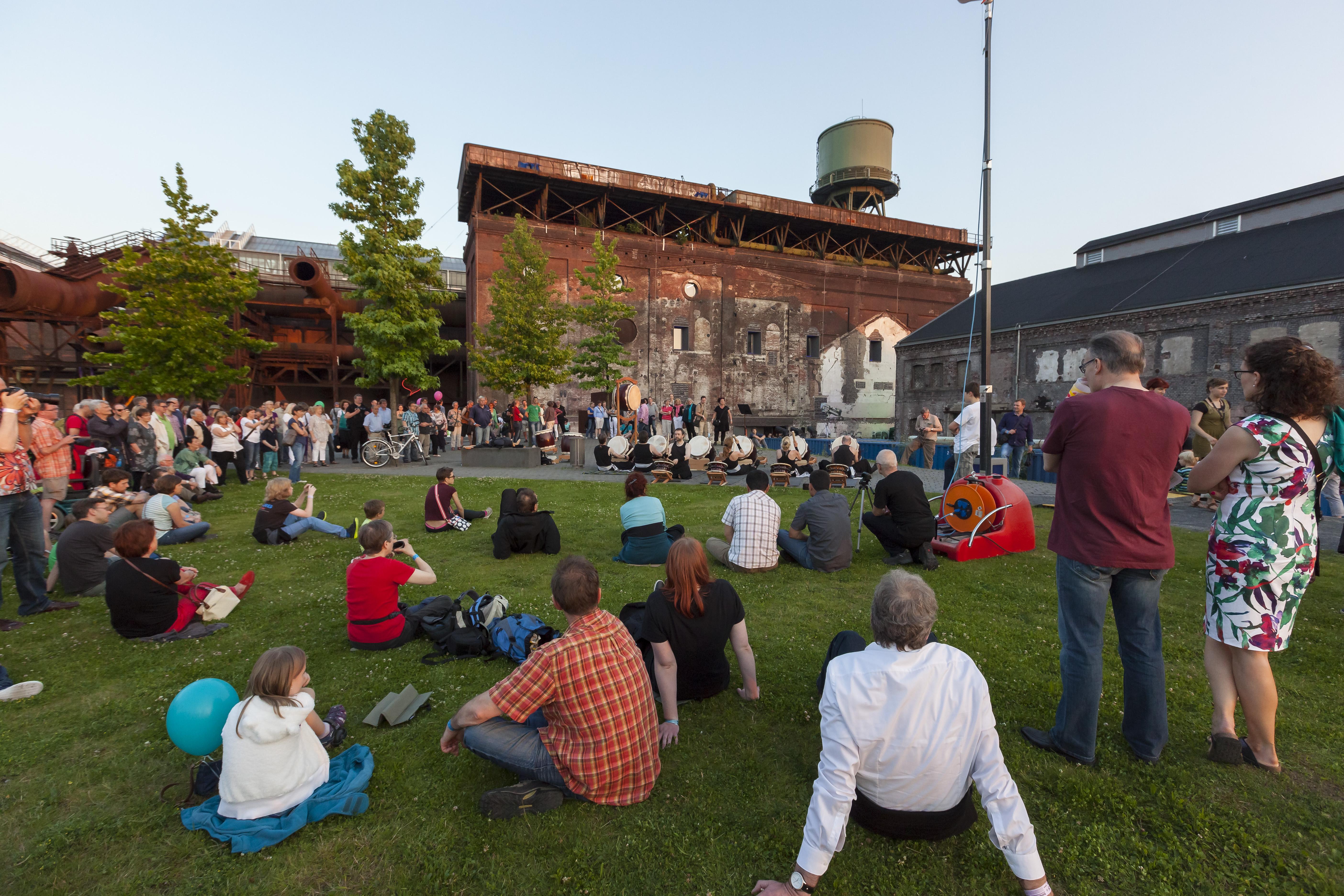 Das Foto zeigt die Jahrhunderthalle Bochum zur ExtraSchicht, wo viele Menschen die Szeneie auf den gemütlichen Wiesen genießen