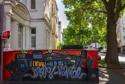 Das Foto zeigt die schönen Fassaden einiger Häuser und eine Graffiti-Wand im Dortmunder Kreuzviertel.