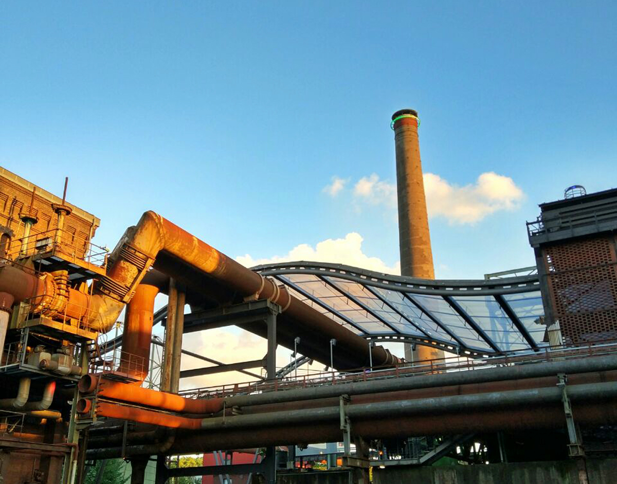 Das Bild zeigt die Industriekulisse und das Glasdach im Landschaftspark Duisburg-Nord