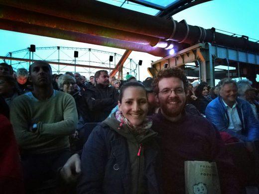 Das Foto zeigt unsere Blogautorin Laura und ihrem Mann, ausgestattet mit Jacken und Popcorn.