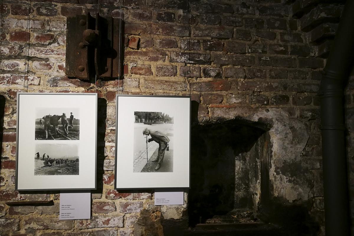 Das Foto zeigt zwei Ausstellungsbilder in schwarz-weiß vor einer alten Backsteinwand.