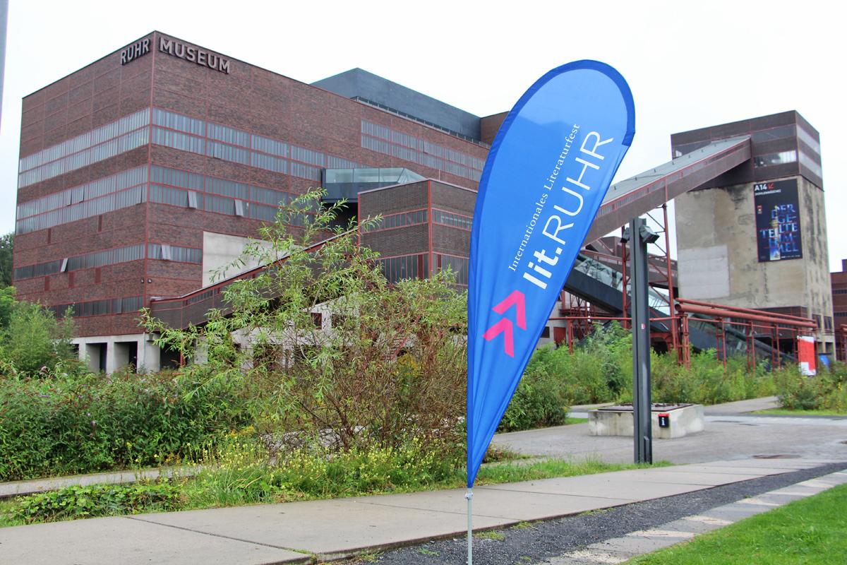Das Bild zeigt das Logo der Lit.Ruhr vor einem Zollverein Gebäude