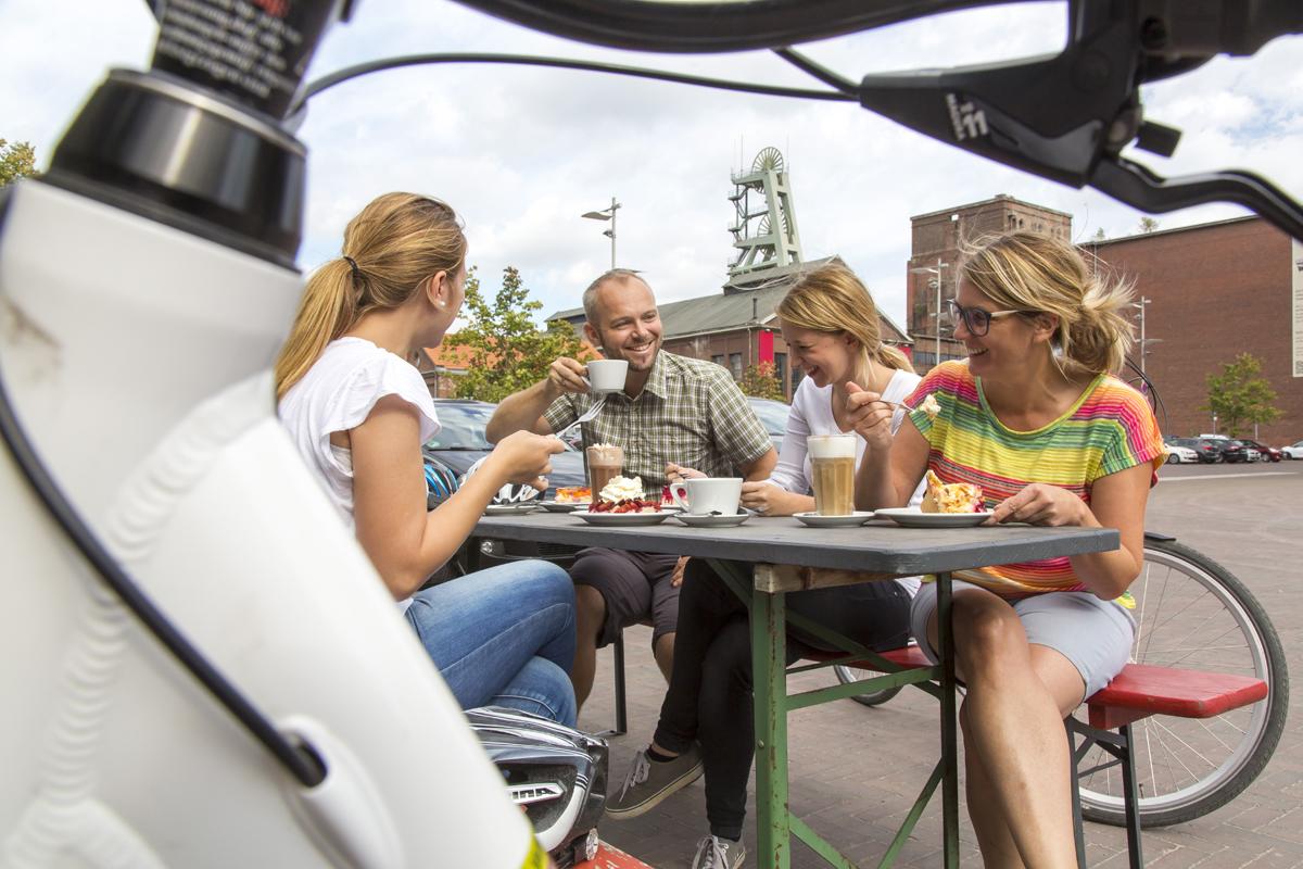 Das Foto zeigt Radfahrer vorm Café Ewald auf dem Geländer der Halde Hoheward in Herten