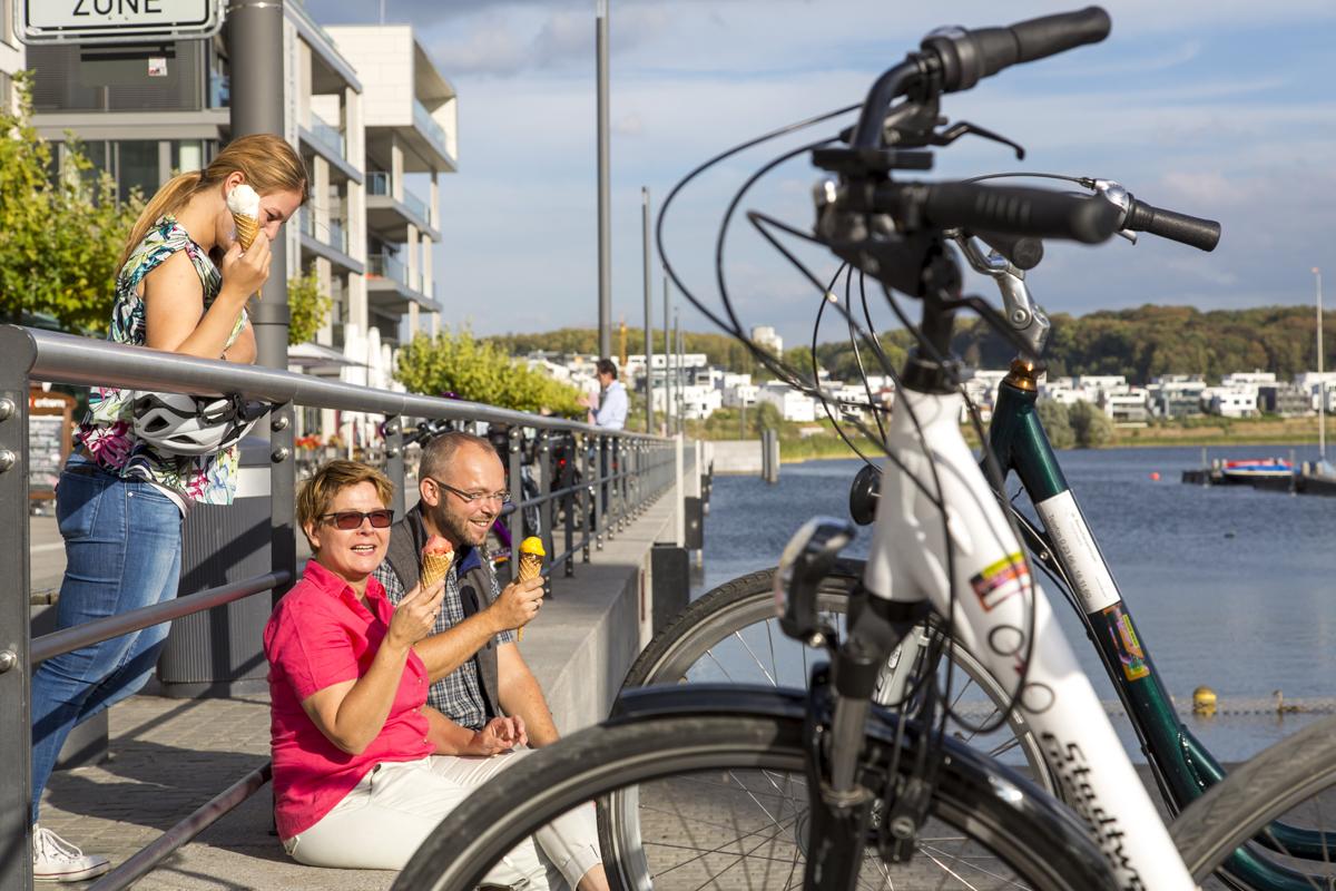 Das Foto zeigt Radfahrer mit Eis am Phoenix See in Dortmund
