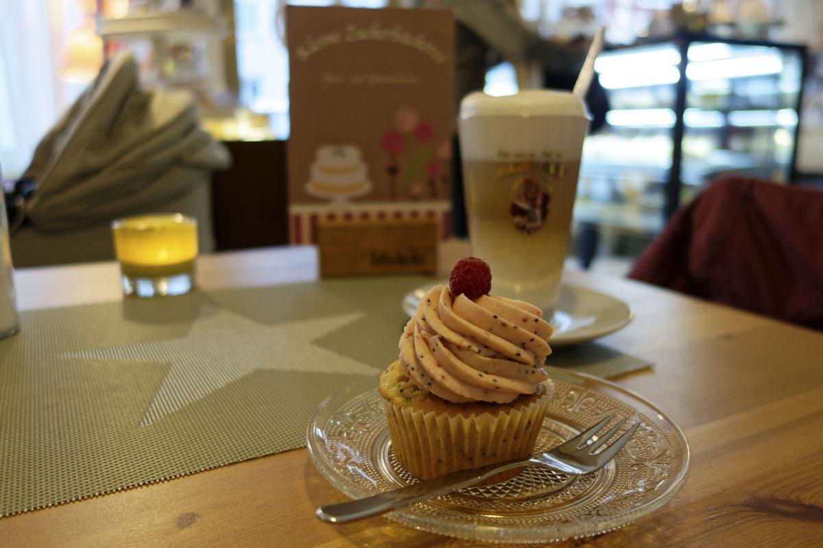 Das Foto zeigt einen Himbeer-Mohn-Cupcake in der Kleinen Zuckerbäckerei