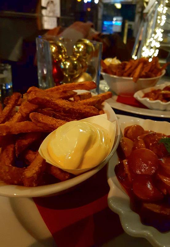 Das Foto zeigt den Klassiker - Currywurst Pommes - im Kokerei Café des UNESCO-Welterbe Zollverein