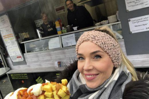 Das Foto zeigt die Blogautorin Sandra mit ihrer Currywurst am Stiel