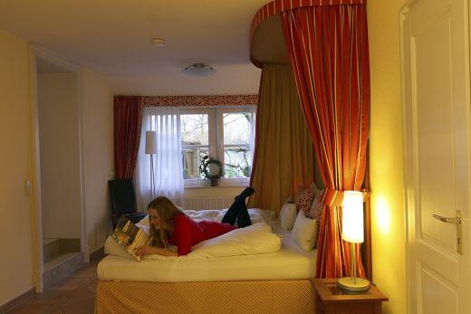 Das Foto zeigt Rebecca beim Lesen im Himmelbett des Wellings Romantik Hotel zur Linde in Moers