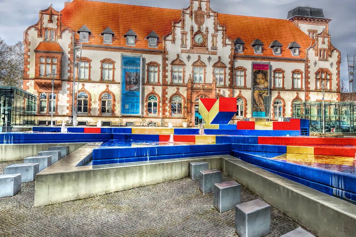 Das Foto zeigt das Kunstmuseum Alte Post mit dem Hajek-Brunnen