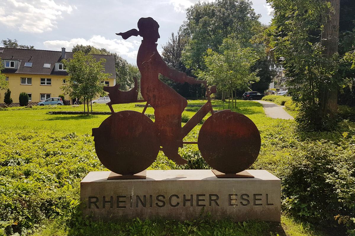 Das Foto zeigt eine Figur einer Radfahrerin auf dem rheinischen Esel