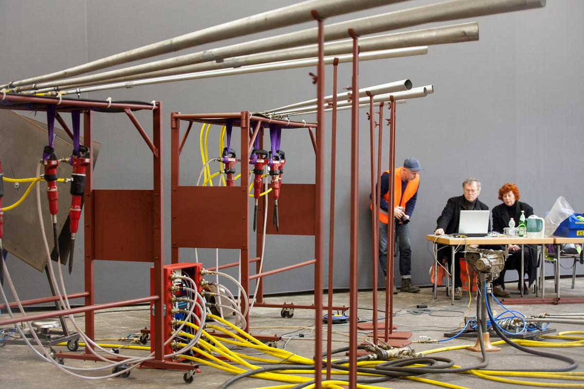 Das Bild zeigt eine Installation aus Abbauhämmern und drei Menschen im Hintergrund