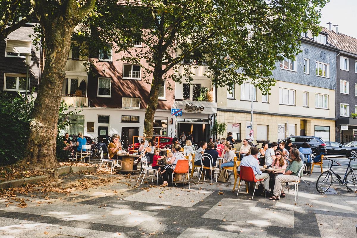 Das Foto zeigt mehrere Tische mit Menschen vor dem I AM LOVE