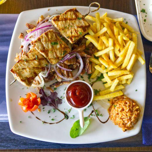 Das Foto zeigt ein Gericht aus Fleisch, Reis und Pommes