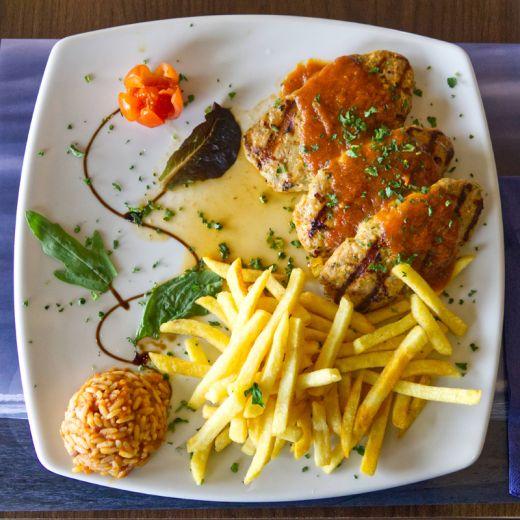 Das Foto zeigt ein Gericht aus Fleisch, Pommes und Reis