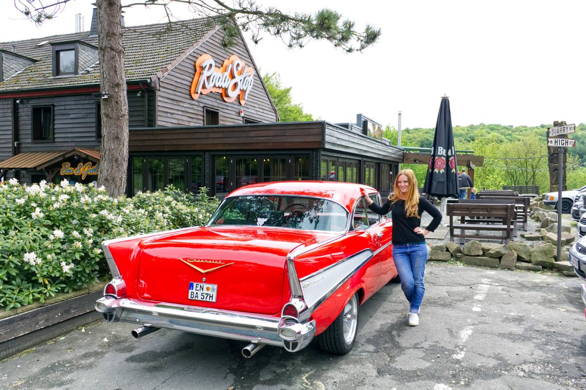 Das Bild zeigt einen roten Chevrolet Oldtimer vor dem Road Stop Motel