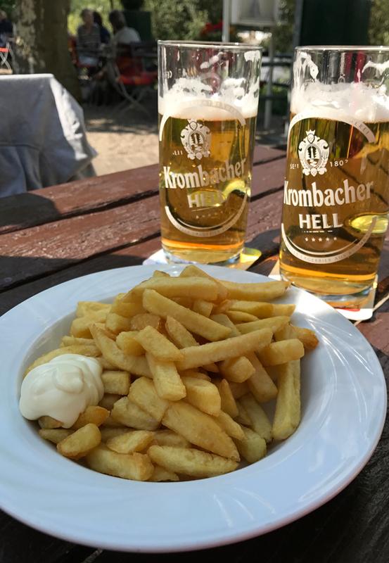 Das Foto zeigt einen Teller Pommes und zwei Gläser Bier