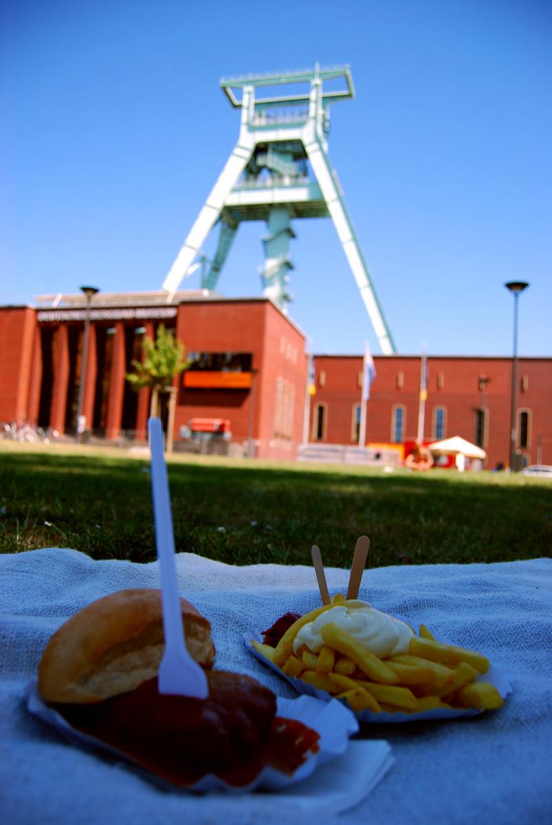 Das Foto zeigt Currywurst-Pommes vor der Kulisse des Deutschen Bergbaumuseums in Bochum