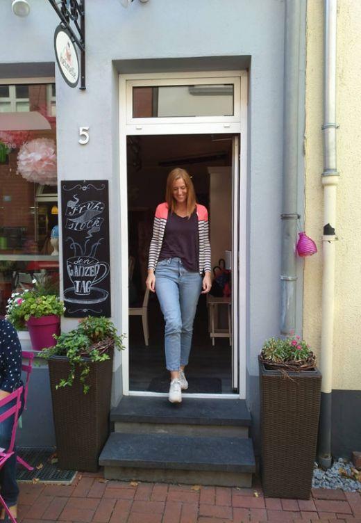 Das Bild zeigt Sarah im Eingang des Cafés heimelie.