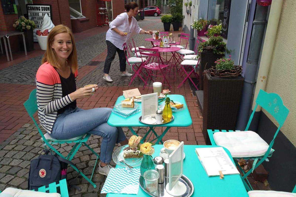Das Bild zeigt Sarah vor dem Café heimelie.