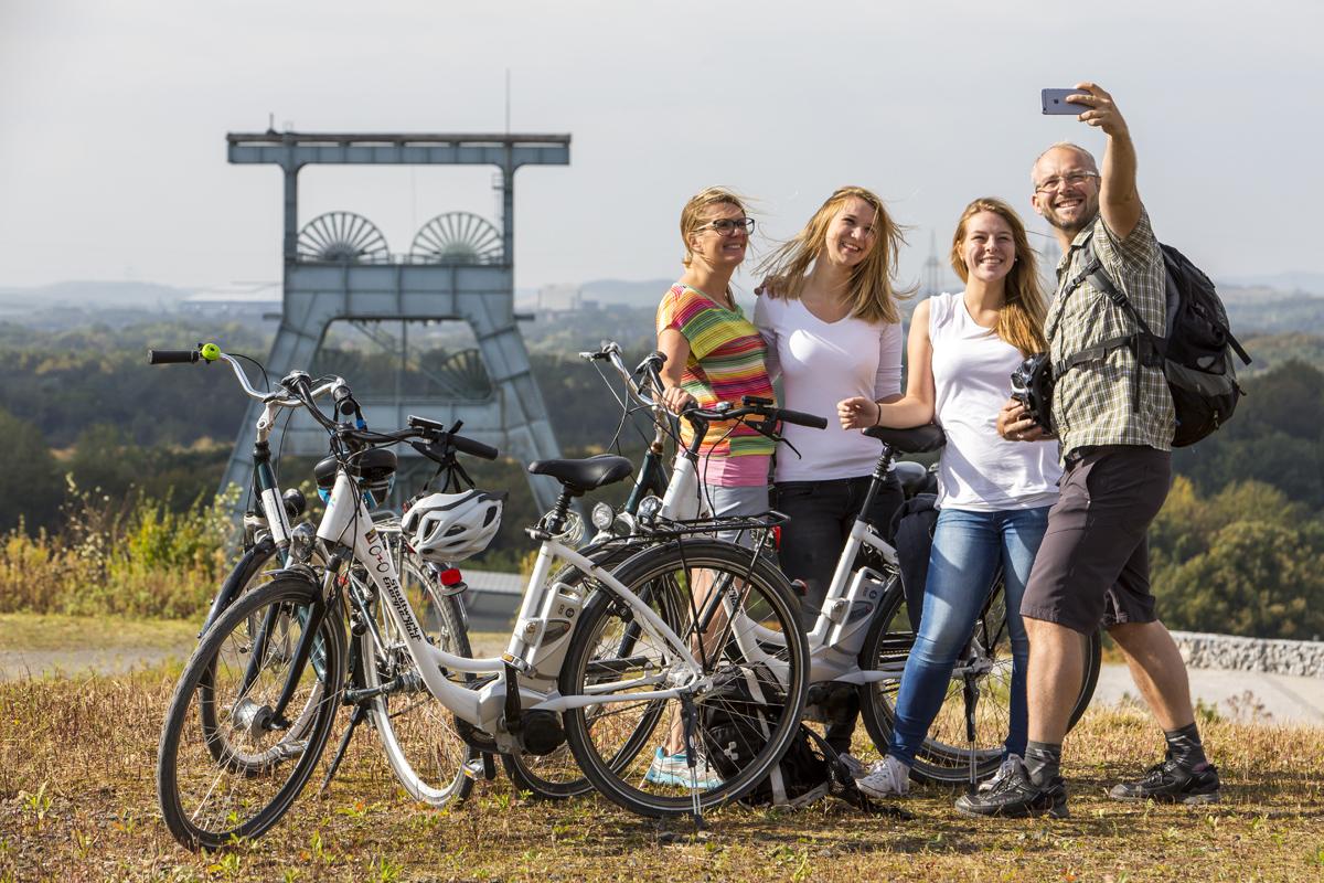 Das Foto zeigt Radfahrer vorm Zechengerüst der Zeche Ewald auf der Halde Hoheward in Herten