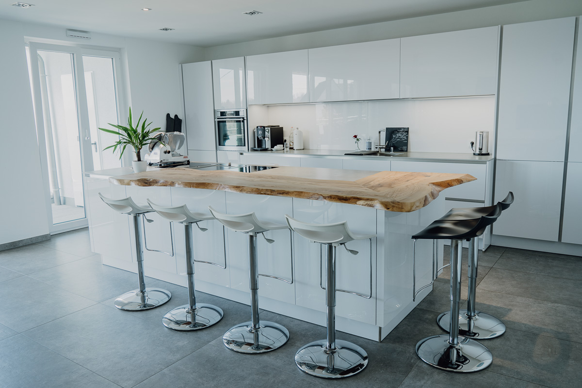 Das Bild zeigt eine Küche mit Theke und Barhockern