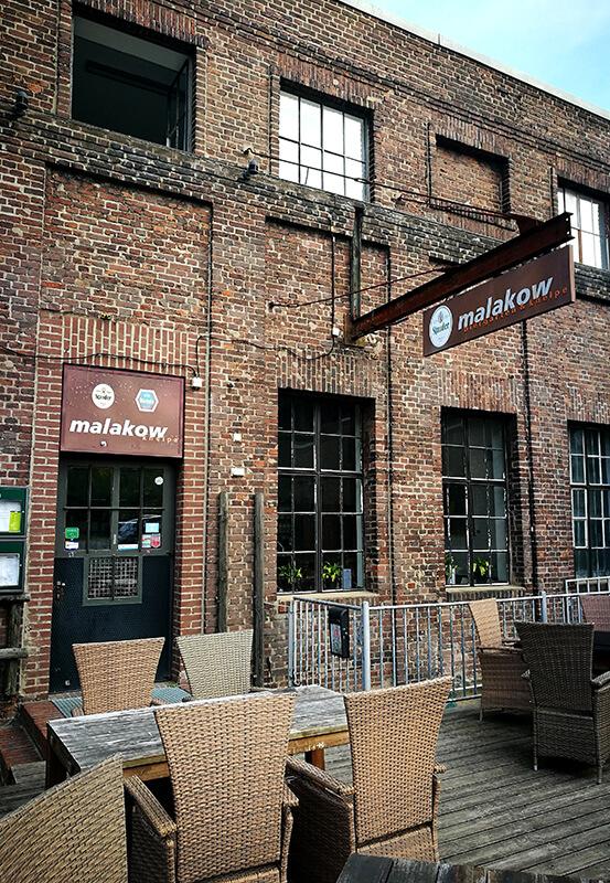 Das Bild zeigt den Eingang und einen Teil des Biergartens des Restaurants Malakow