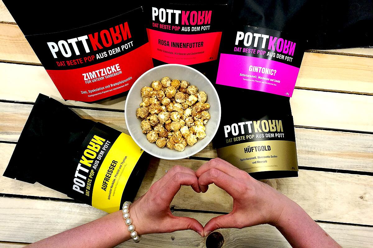 Das Bild zeigt ein Schälchen Popcorn, verschiedene POTTKORN-Tüten und ein Herz aus Händen geformt