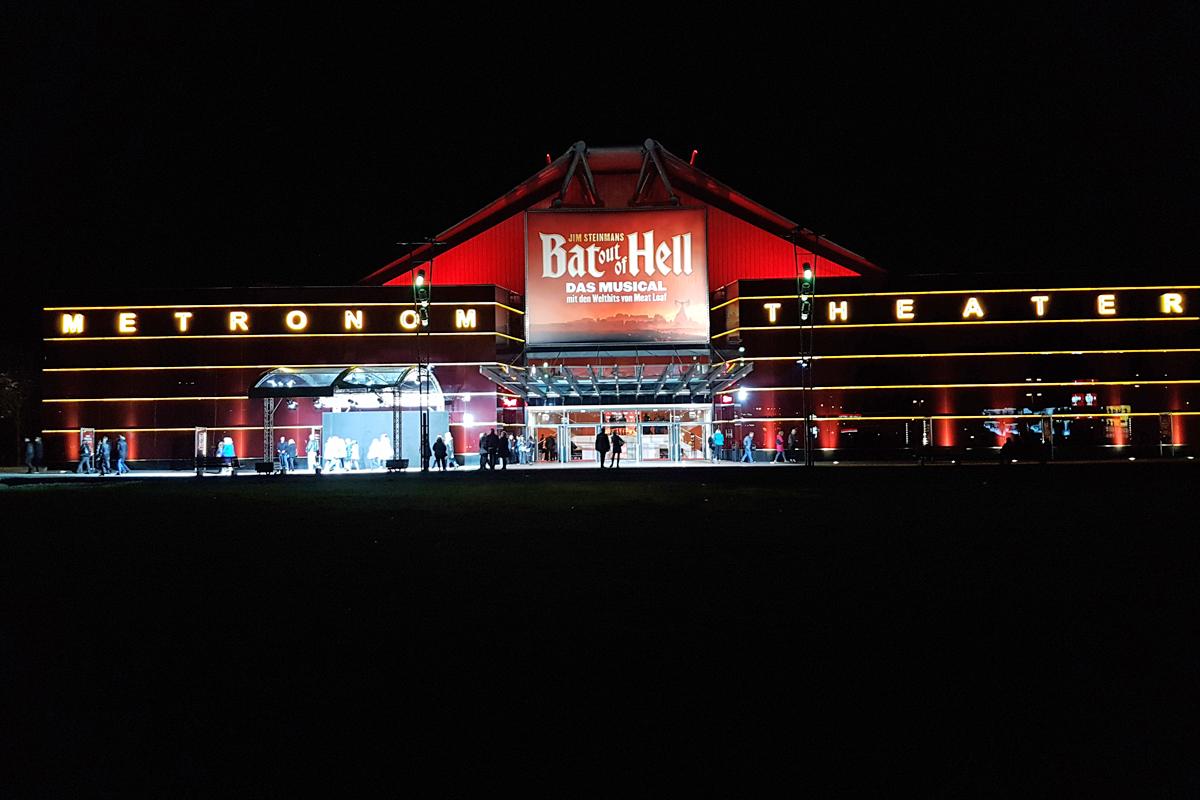Ganz in rot leuchtet das Metronom Theater in Oberhausen bei Nacht