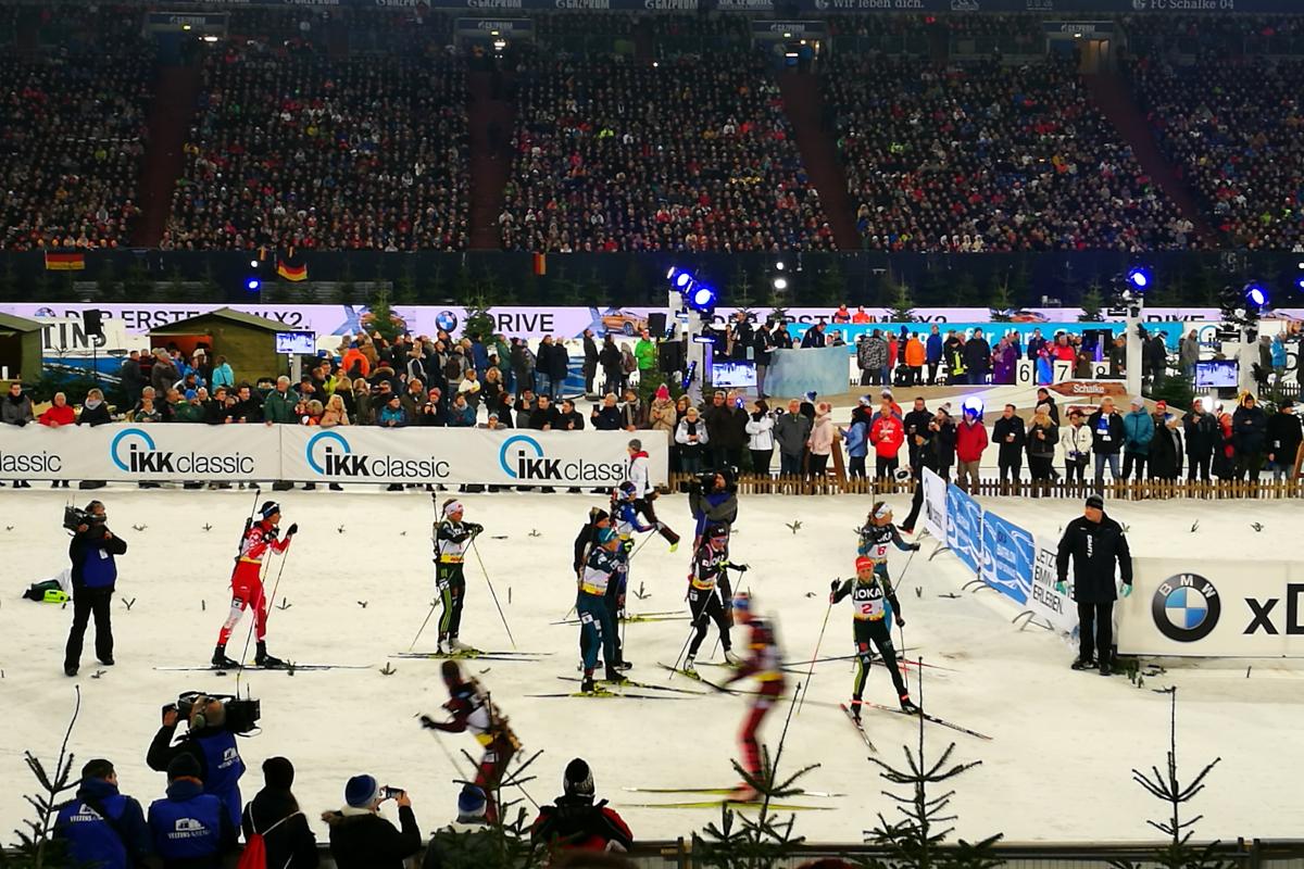 Das Bild zeigt die Übergabe des Staffelstabs beim Biathlon auf Schalke