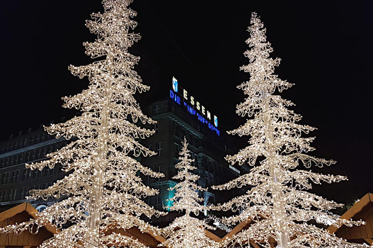 Das Bild zeigt zwei Lichter-Weihnachtsbäume auf dem Weihnachtsmarkt in Essen.
