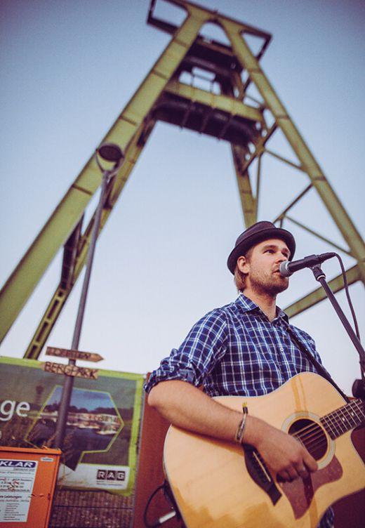 Das Bild zeigt einen Mann mit Gitarre vor dem Fördergerüst auf der Zeche Lohberg.