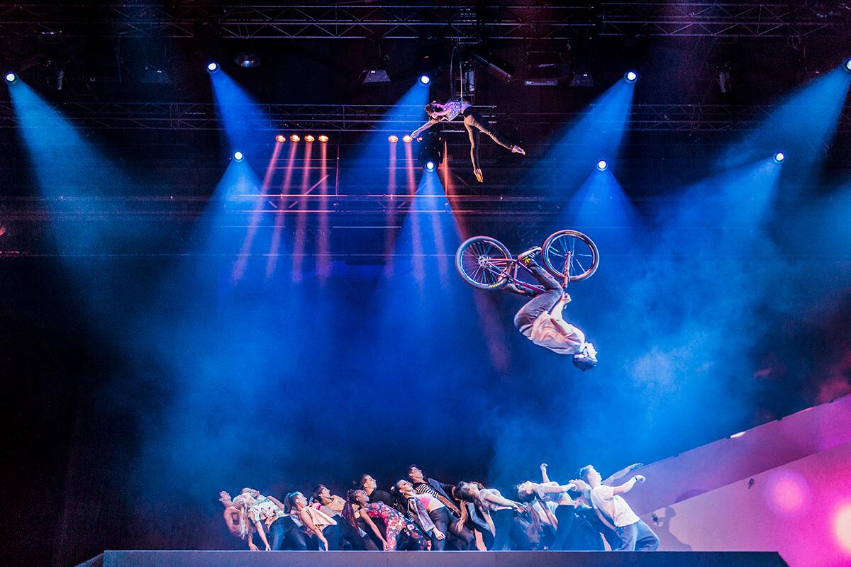 Das Bild zeigt eine Gruppe Tänzer und darüber einen BMXler, der einen Salto macht.