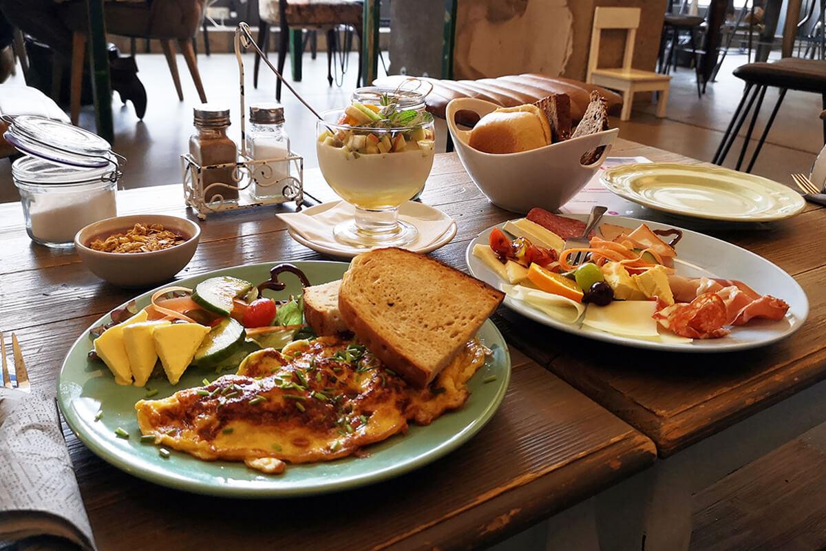 Das Bild zeigt einen Teller mit Rührei, Brötchen und Salatbeilage.