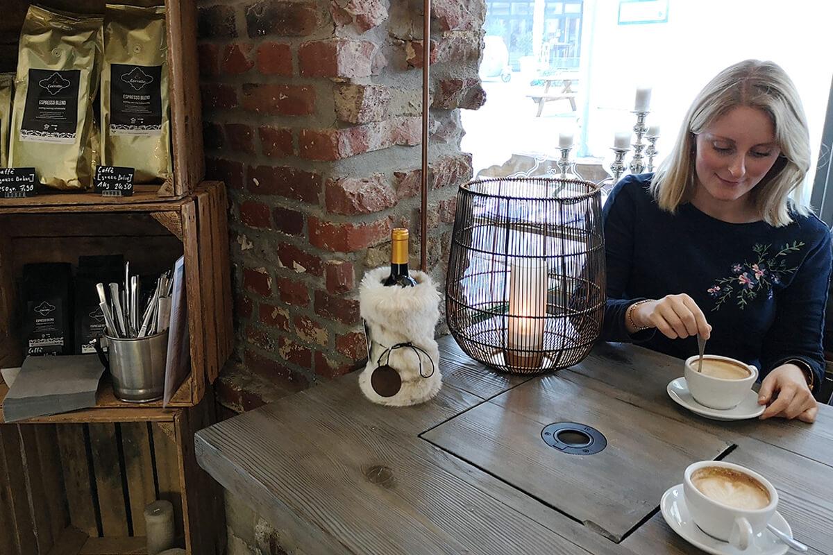 Das Bild zeigt die Autorin mit einem Cappuccino im Coretto.