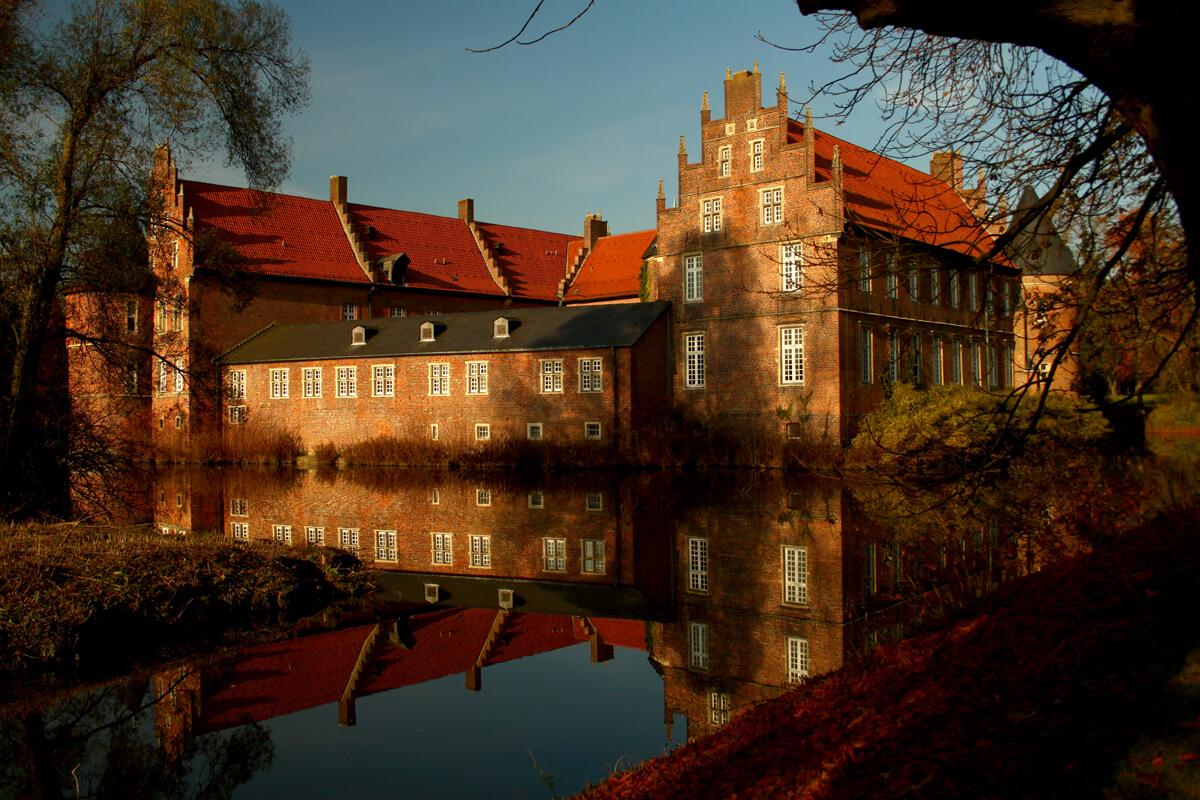 Das Bild zeigt das Schloss Herten, dass sich im Wassergraben spiegelt