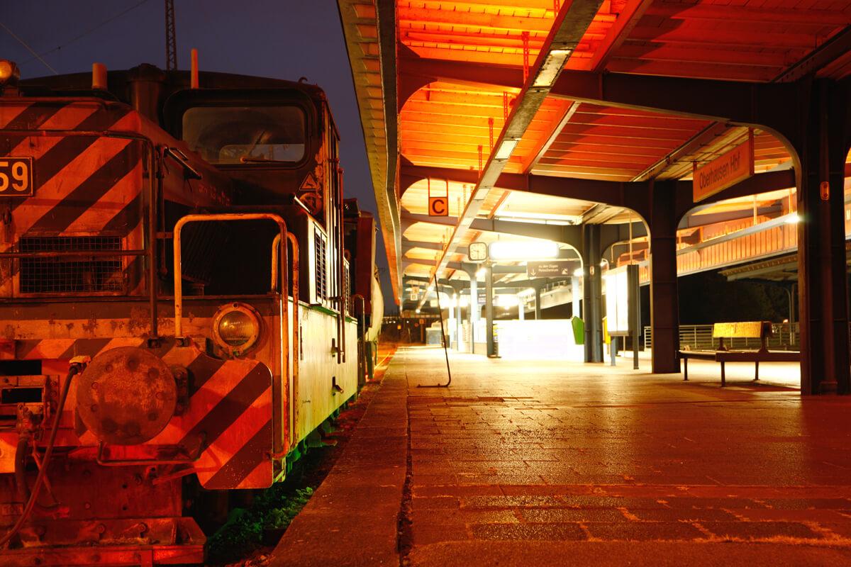 Das Bild zeigt eine Lok bei Nacht auf einem Bahnsteig