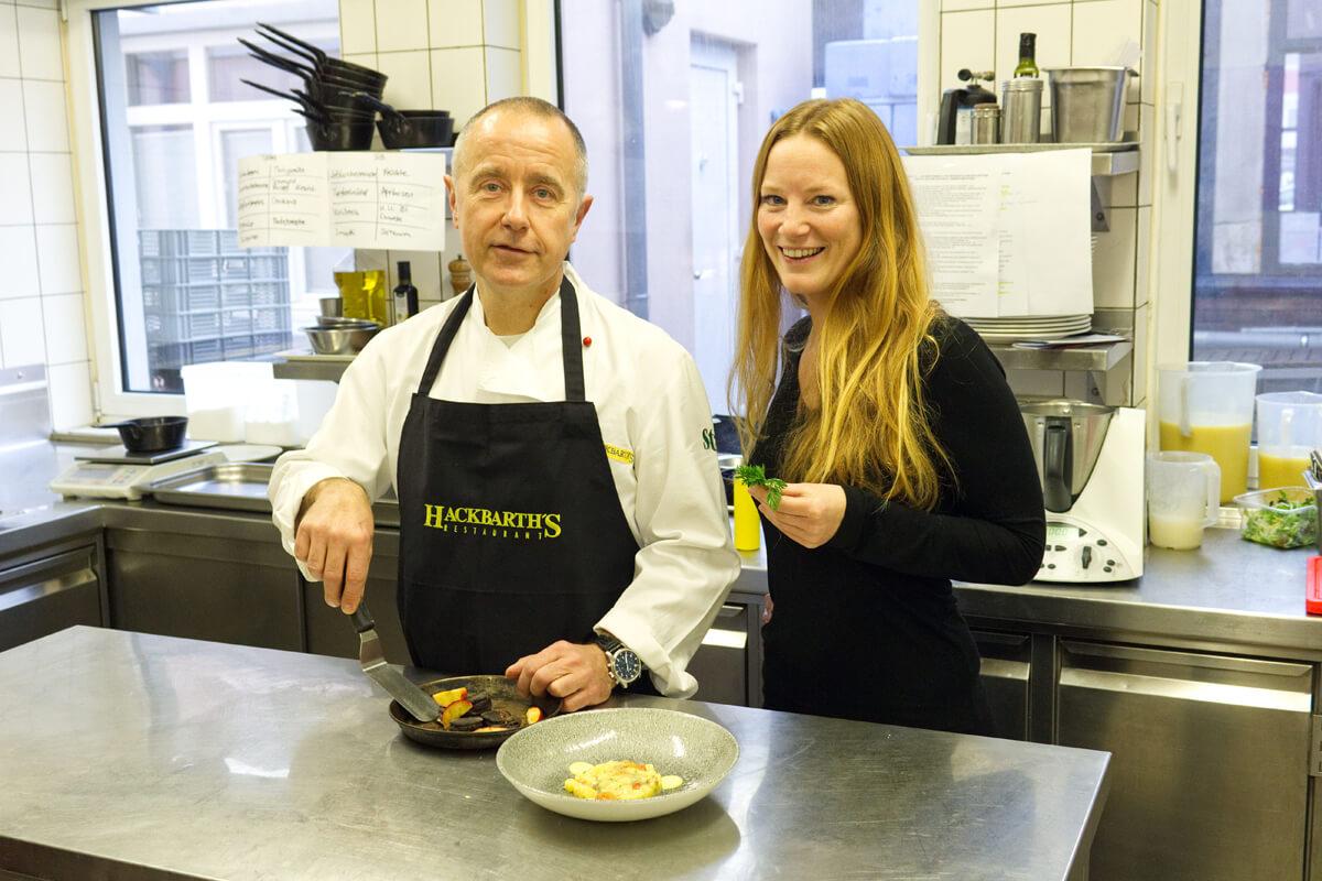 Das Bild zeigt die Autorin Rebecca in der Küche mit dem Koch.