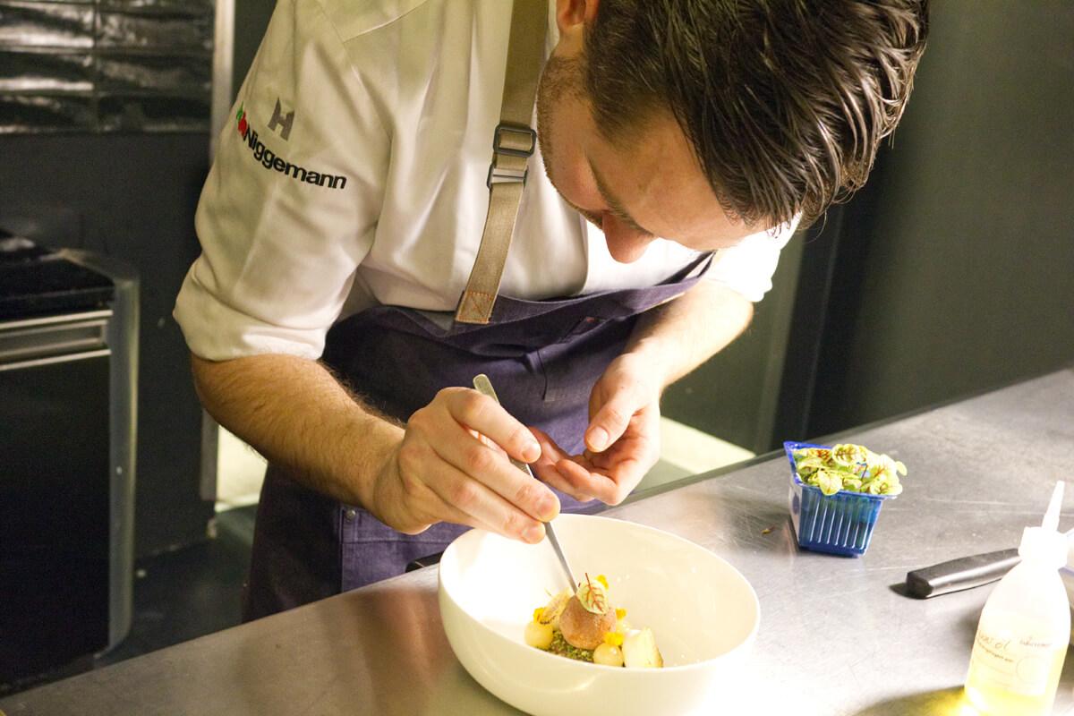 Das Bild zeigt einen Mitarbeiter des Restaurants beim Dekorieren eines Tellers.