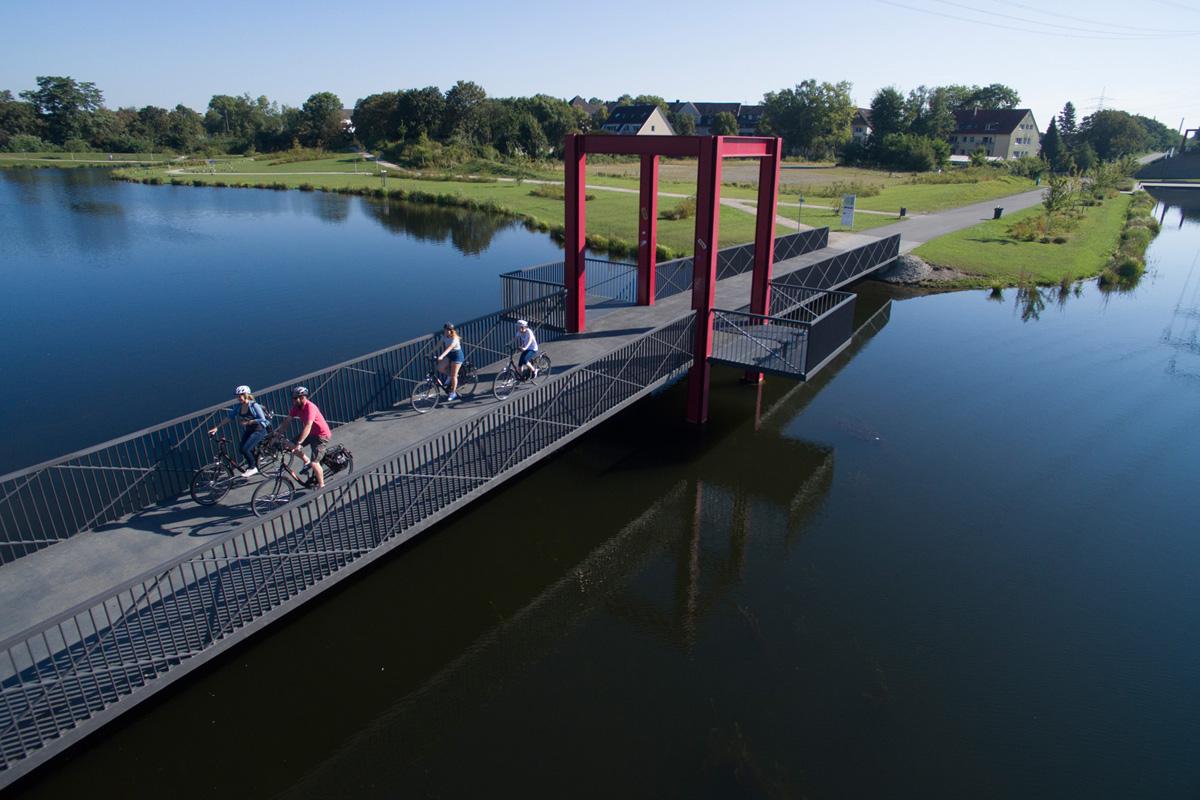 Das Foto zeigt Radler auf einer Brücke über den Niederfeldsee