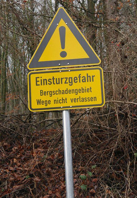 """Das Foto zeigt ein Hinweisschild """"Einsturzgefaht Bergschadengebiet Wege nicht verlassen"""" in Bochum"""